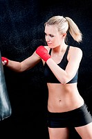 Boxing training blond woman sparring punching bag