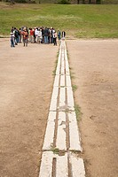 Tourists at the starting line of the original Olympic Stadium, Olympia, Greece