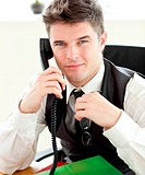 Attentive businessman talking on phone looking at the camera
