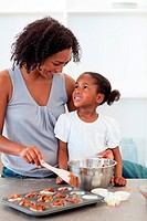Happy mother helping her daughter cooking biscuits
