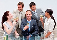 Smiling business team celebrating a success with champagne