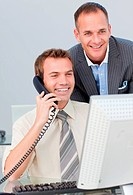 Businessman on phone and working with his colleague