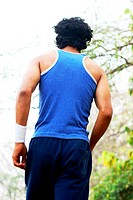 Rear view of a man jogging , partial view