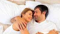 Affectio te couple hugging lying in bed