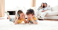 Laughing children listening music with headphones