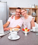 Affectio te couple using a laptop while having breakfast