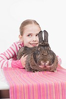 Girl holding rabbit, smiling (thumbnail)