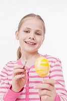 Girl colouring easter egg, smiling
