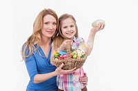Mother and daughter with easter egg basket, smiling, portrait