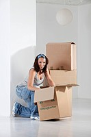 Young woman packing cardboard box, smiling, portrait (thumbnail)