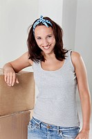 Young woman leaning at cardboard box, smiling, portrait