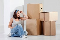 Young woman sitting by cardboard box, smiling