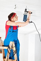 Germany, Bavaria, Young woman drilling with electric drill