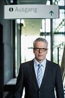 Germany, Stuttgart, Businessman standing in office building, portrait