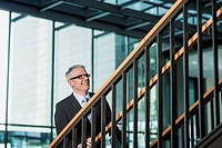 Germany, Stuttgart, Businessman moving up on office staircase