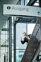 Germany, Stuttgart, Businessman moving up on office staircase, portrait, smiling (thumbnail)