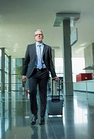 Germany, Stuttgart, Businessman pulling luggage in office building (thumbnail)