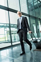 Germany, Stuttgart, Businessman pulling luggage in office building