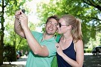 Germany, North Rhine Westphalia, Duesseldorf, Couple taking photo of themselves, smiling