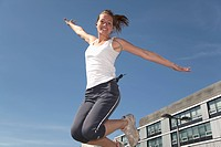 Germany, North_Rhine_westphalia, Duesseldorf, Young woman jump in air, smiling, portrait