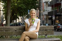 Germany, North Rhine Westphalia, Cologne, Young woman sitting on bench with coffee cup, smiling, portrait