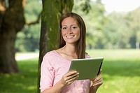 Germany, North Rhine Westphalia, Cologne, Young woman in park with digital tablet, smiling, portrait