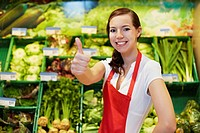Germany, Cologne, Young woman showing thumbs up in supermarket, smiling, portrait