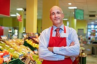 Germany, Cologne, Mature man standing in supermarket, smiling, portrait (thumbnail)