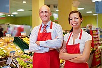 Germany, Cologne, Man and woman standing in supermarket, smiling, portrait