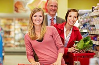 Germany, Cologne, Man and women in supermarket, smiling, portrait