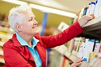 Germany, Cologne, Mature woman in supermarket, smiling
