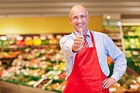 Germany, Cologne, Mature man showing thumbs up in supermarket