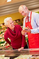 Germany, Cologne, Mature couple with premade salad in supermarket