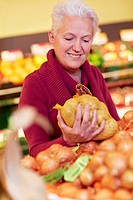 Germany, Cologne, Mature woman holding potatoes bag in supermarket