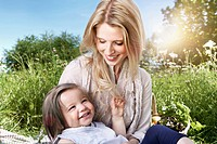 Germany, Cologne, Mother and daughter sitting on meadow, smiling