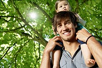 Germany, Cologne, Father carrying daughter on shoulders, smiling