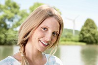 Germany, Cologne, Young woman smiling, portrait, wind turbine in background