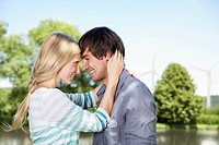 Germany, Cologne, Young couple embracing, smiling