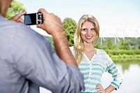 Germany, Cologne, Young man taking photo of woman