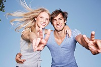 Germany, Cologne, Young couple showing peace sign, smiling, portrait (thumbnail)