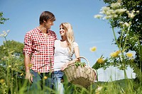 Germany, Cologne, Young couple with picnic basket in meadow, smiling
