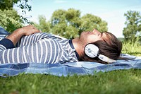Germany, Cologne, Young man listening music in meadow