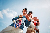 Low angle view of two young men standing with a skate board