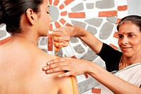 Young woman getting oil massage done