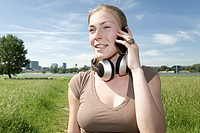 Germany, North Rhine Westphalia, Duesseldorf, Young woman talking on phone,smiling