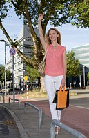 Europe, Germany, North Rhine Westphalia, Duesseldorf, Mid adult woman hailing taxi, smiling