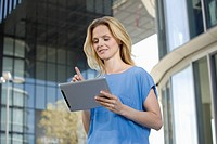 Europe, Germany, North Rhine Westphalia, Duesseldorf, Businesswoman using digital tablet, smiling