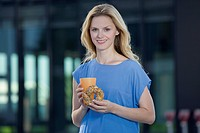Europe, Germany, North Rhine Westphalia, Duesseldorf, Mid adult woman with food and drink, smiling