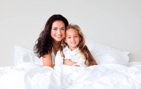 Confident mother and her daughter looking at the camera on the bed