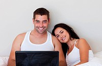 Happy couple using a laptop on the bed